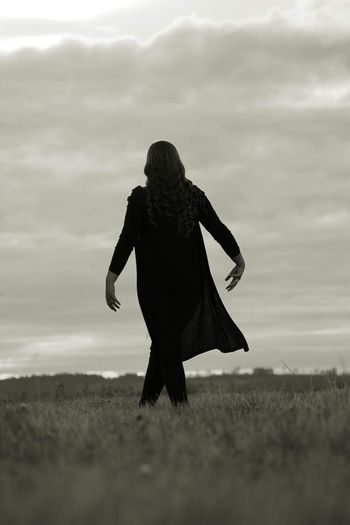 Surface level view of woman dancing on grassy field