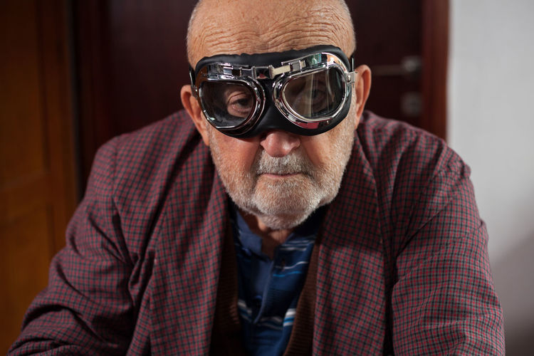 funny old man with pilot glasses and pajamas Bearded Casual Clothing Close-up Face Front View Funny Grandfather Grimace Grimacing Indoors  Joking Lifestyles Looking At Camera Pajamas Pensioner Pilot Glasses Portrait Posing Retired Retirement Senior Adult Senior Men Sitting Veteran Wrinkled