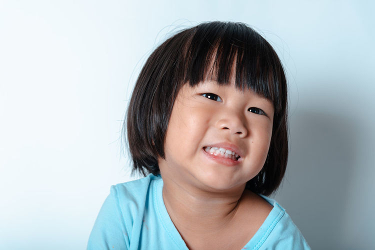 Portrait of smiling boy against white background