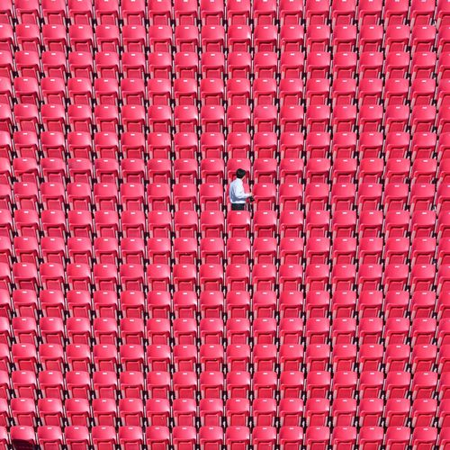 Man Standing Amidst Red Chairs At Stadium
