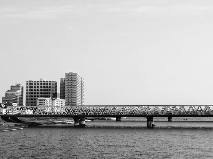 Bridge over river in city against clear sky