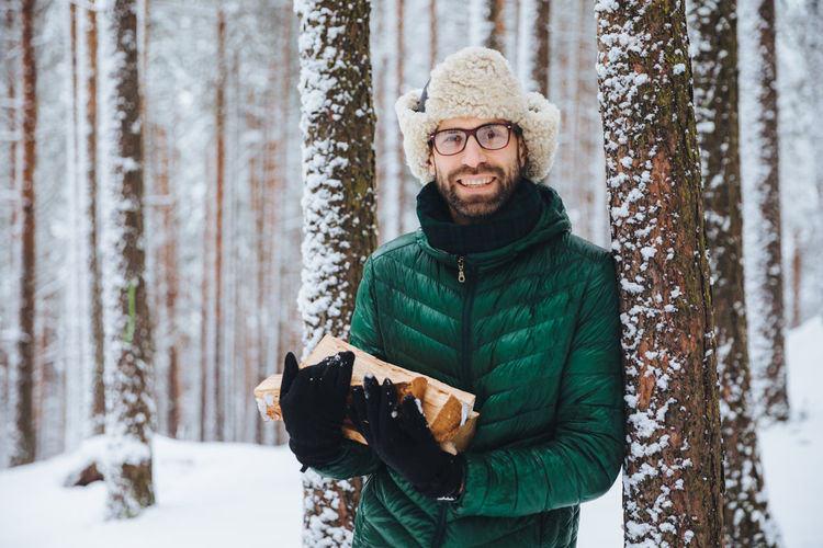 Portrait of smiling man standing in snow