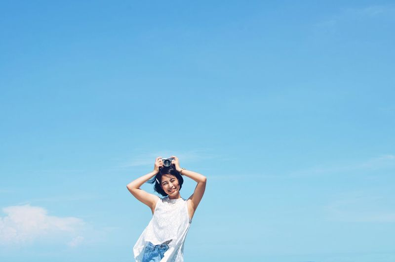 Low angle view of young woman standing against blue sky