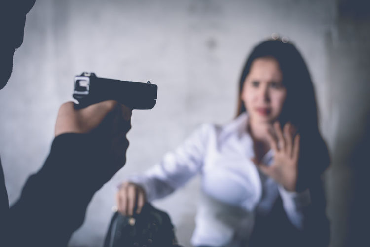 Midsection Of Man Pointing Gun Towards Woman At Night