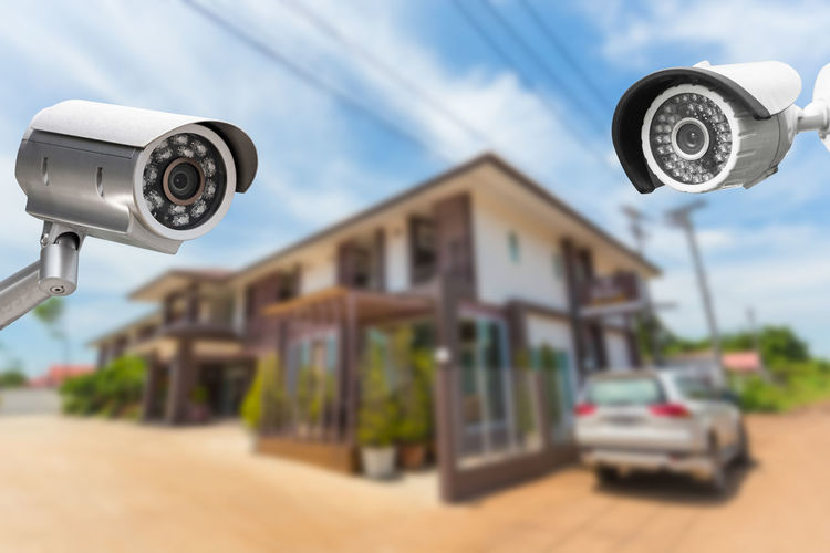 Close-Up Of Security Cameras Against House