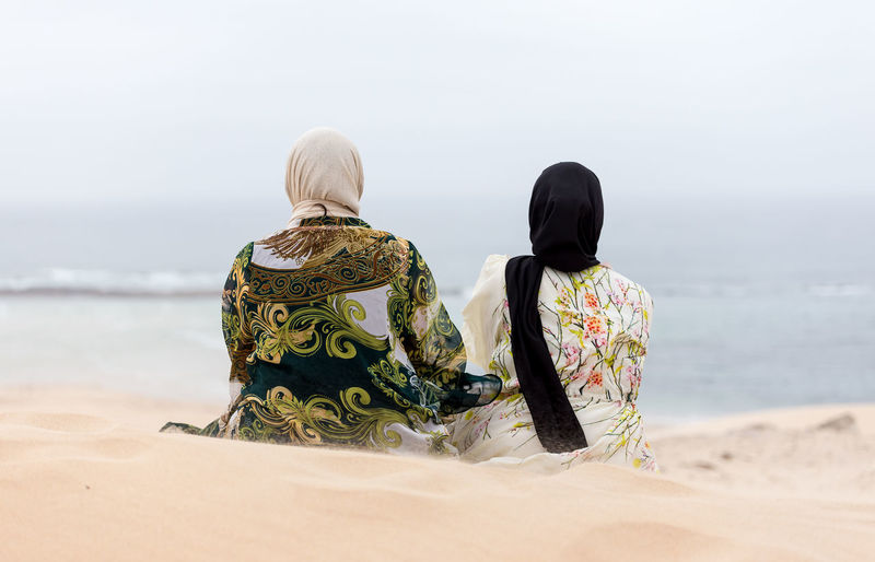 Rear view of women looking at sea while sitting on sand