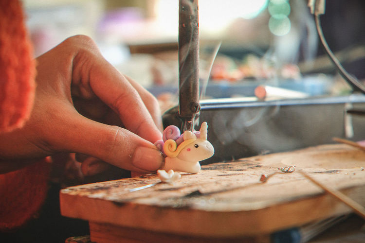Cropped image of artist making figurine at factory