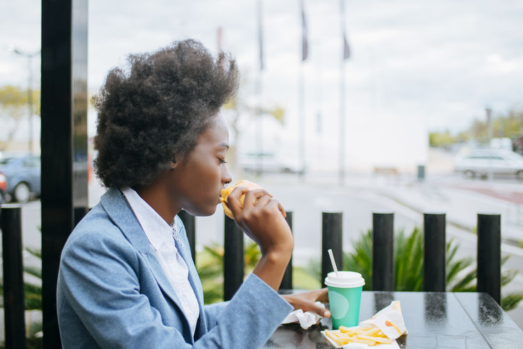 Young woman eating a cheeseburger. Afro Fast Food Food And Drink Woman Afrohair Black Hair Businesswoman Bussiness Drink Food Food And Drink Hamburger Lifestyles One Person Outside Real People Young Adult