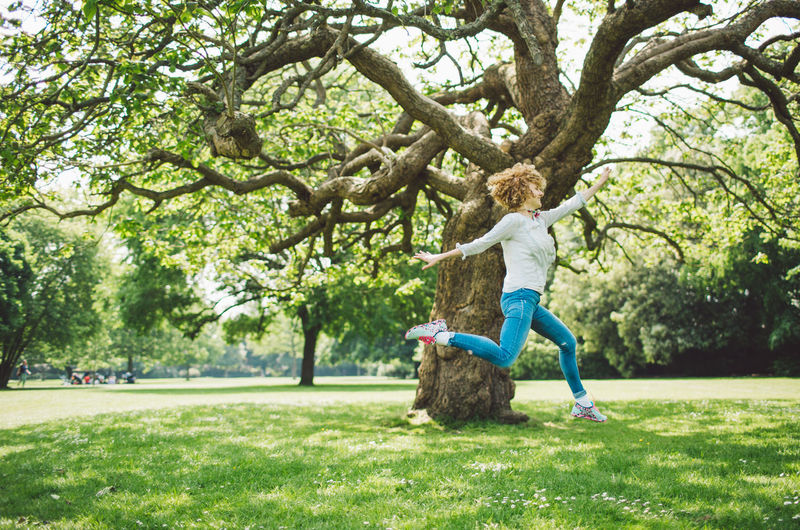 Side View Of Happy Woman With Arms Raised Jumping In Park