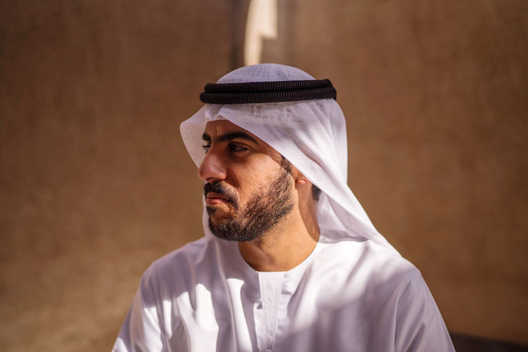 Portrait of arab man wearing dishdash kandura standing in historical disctrict