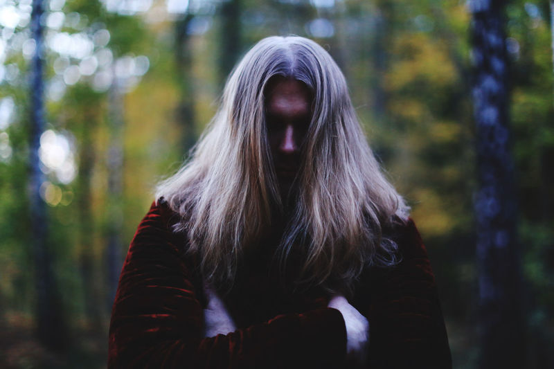 Man with long hair standing in forest
