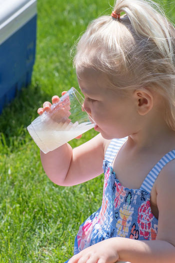 Close-up of cute girl drinking juice in park during sunny day