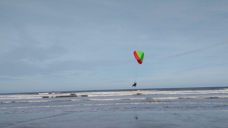 Paraglider paragliding over sea against sky