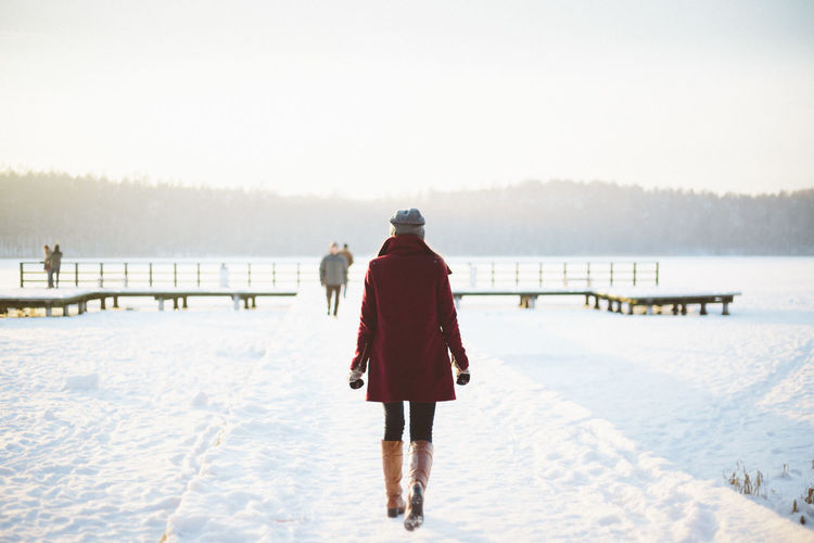 Beauty In Nature Clear Sky Cold Temperature Day Full Length Jetty Lake Nature Outdoors Pier Rear View Remote Scenics Sea Solitude Tranquil Scene Tranquility Vacations Water Weekend Activities Winter