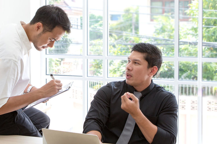 Businessmen discussing while sitting in office