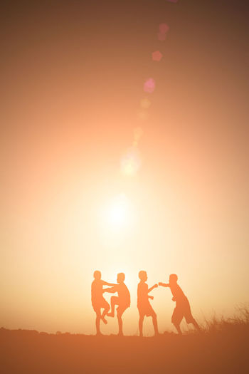 Silhouette boys playing on field against sky during sunset