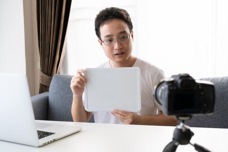 Man holding blank placard while vlogging