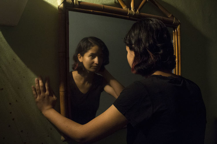 She and the Mirror HUAWEI Photo Award: After Dark Portrait Of A Woman Adult Casual Clothing Emotion Indoors  Lifestyles Mirror Night Nightlife People Portrait Real People Serious Standing Waist Up Women Young Adult Young Women