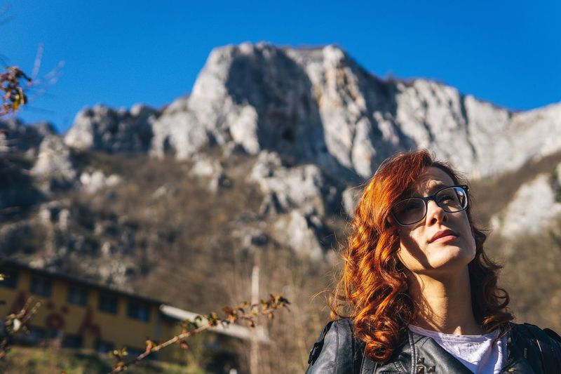 Portrait of young woman in sunglasses against mountains