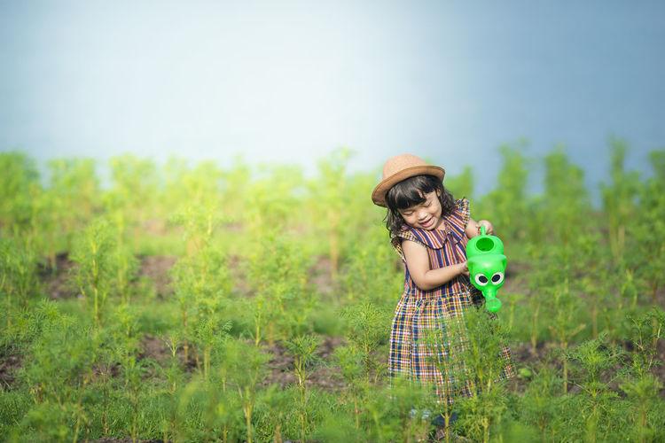 Girl watering plants on field