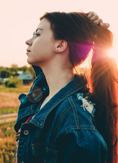 Thoughtful young woman looking away while standing on land