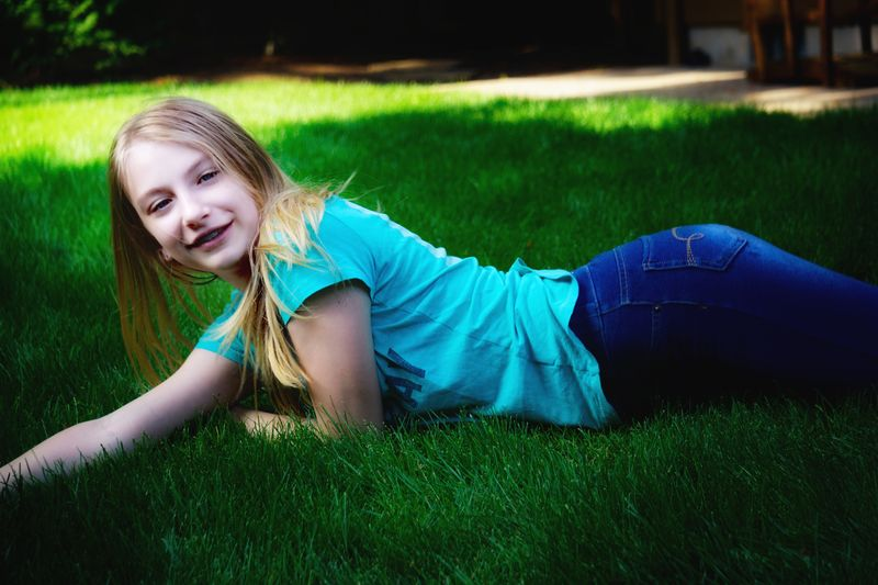 Portrait of smiling girl on grassy field