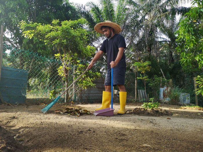 Full length of man cleaning field with broom