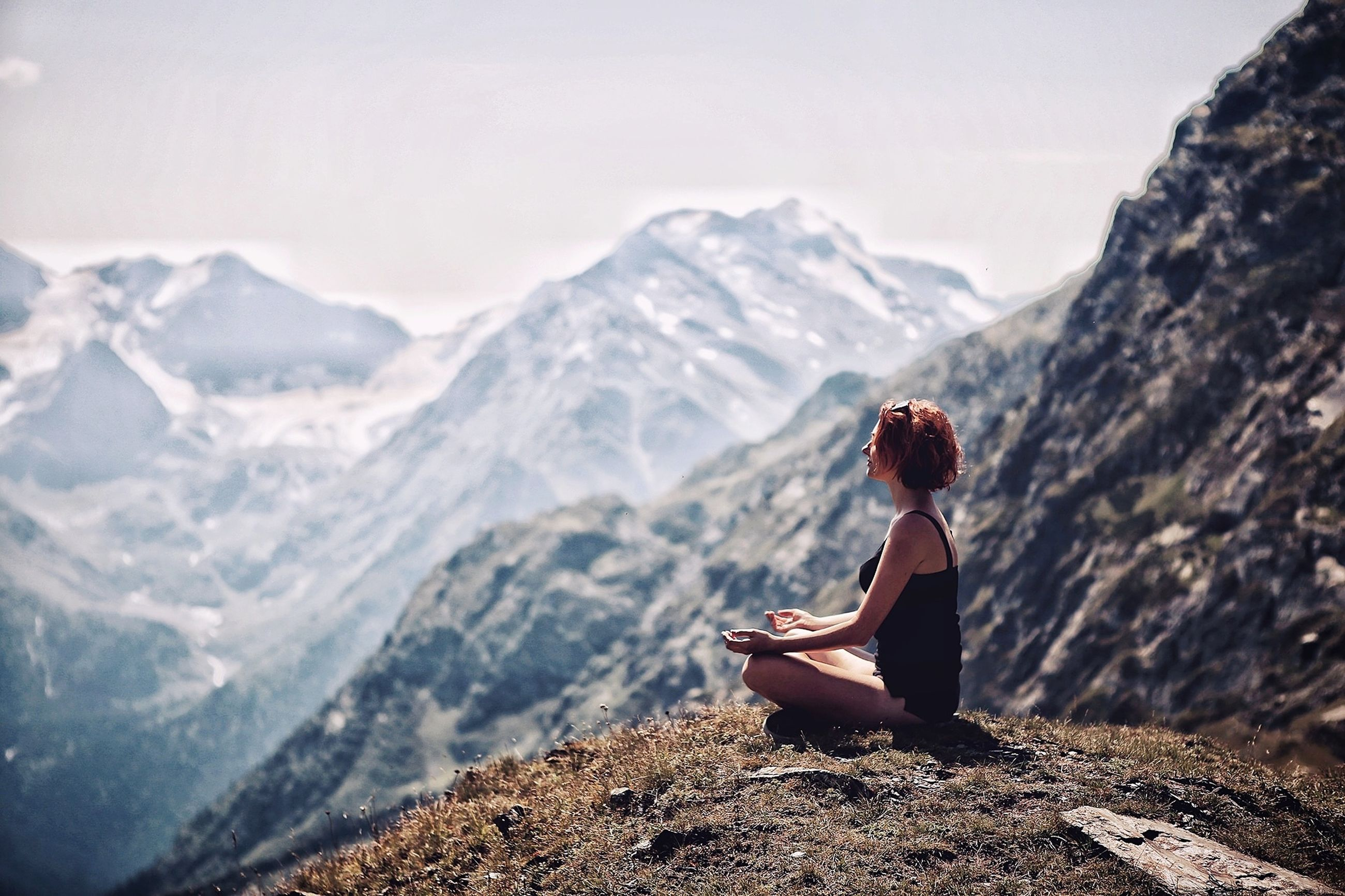 mountain, one person, leisure activity, real people, scenics - nature, beauty in nature, lifestyles, sitting, rock, rock - object, mountain range, solid, tranquility, nature, non-urban scene, young adult, tranquil scene, day, women, outdoors