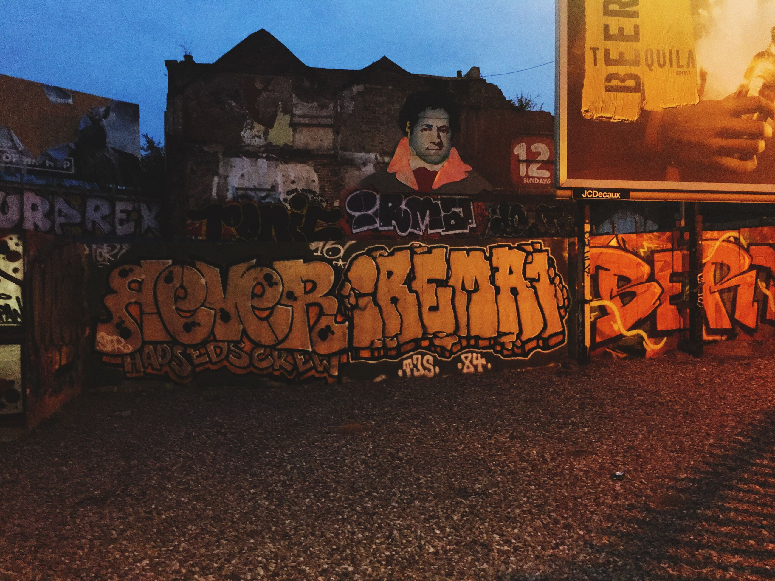 architecture, built structure, building exterior, graffiti, text, clear sky, western script, building, outdoors, creativity, sky, city life, no people