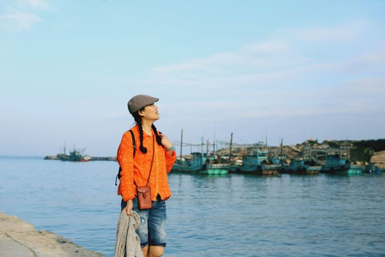 Woman standing at harbor against sky