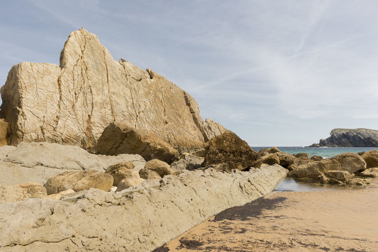 Rock Formations On Beach Against Sky