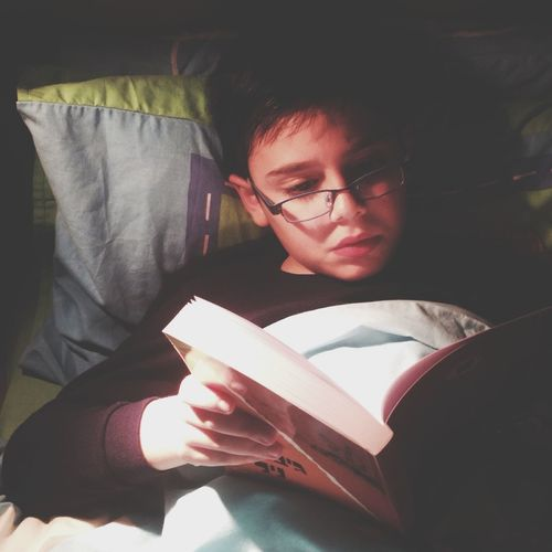 Close-up of boy reading book at home