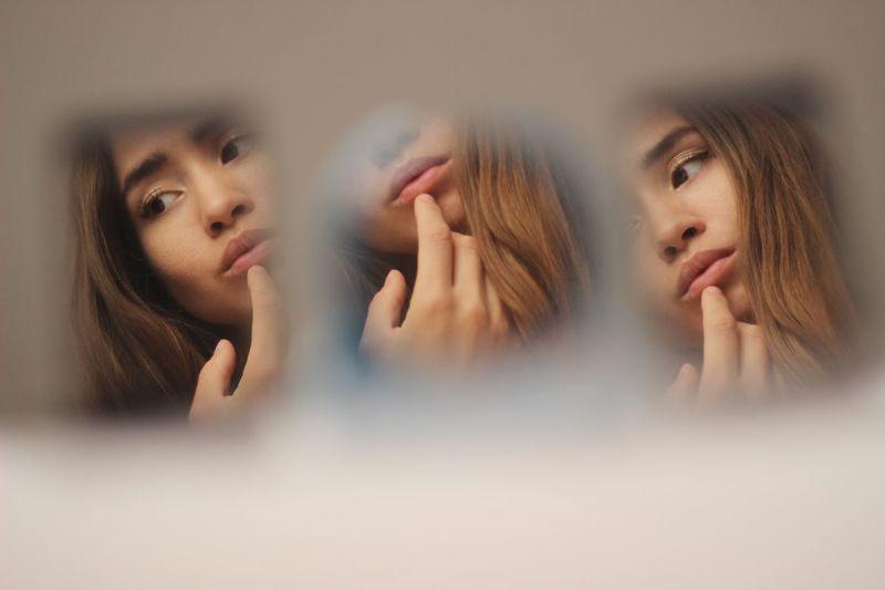 Reflection of woman touching lips