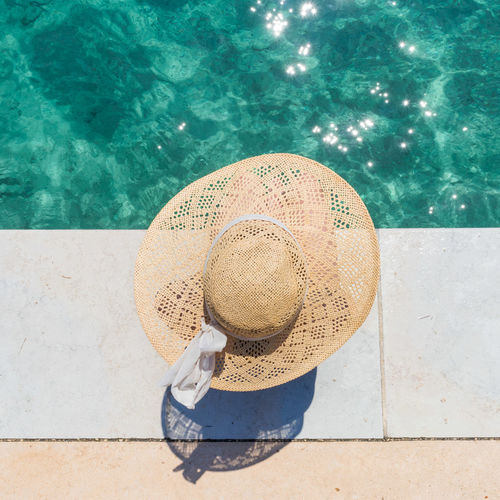 Directly above shot of woman wearing hat sitting at poolside