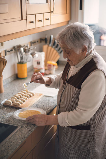 High angle view of senior woman preparing food on kitchen counter