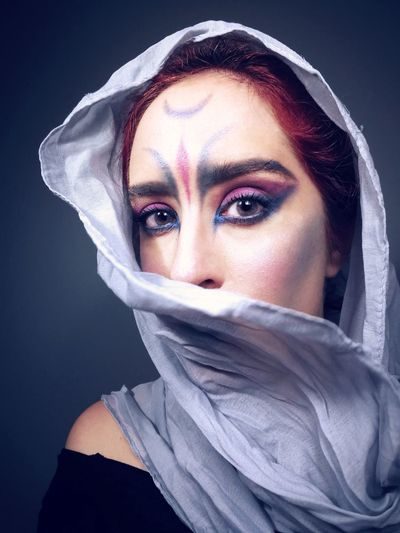 Close-up portrait of young woman with make-up over black background