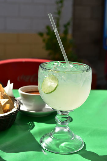 Large glass of lemonade with lime slice in glass served in mexican restaurant