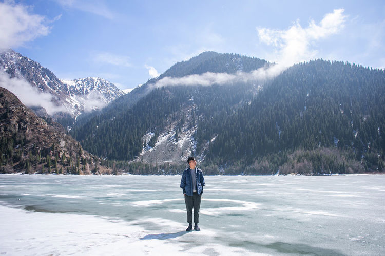Man standing on frozen lake against mountains and sky