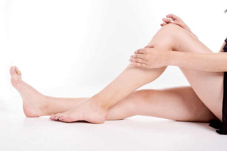 Woman holding on leg. Beautiful fit long female legs, isolated on white background. Spa woman touching her slim legs. Adult, Arm, Attractive, Background, Barefoot, Beautiful, Beauty, Body, Care, Caucasian, Clean, Closeup, Cosmetic, Elegance, Fashion, Female, Foot, Fresh, Freshness, Girl, Hand, Hands, Health, Healthy, Human, Isolated, Leg, Legs, Long, Medicine, Model, Nak barefoot Beautiful Woman Close-up Human Body Part Human Leg Human Skin Lifestyles Low Section One Person People Relaxation Studio Shot White Background Women Young Adult Young Women