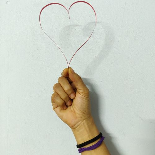 Close-up of hand holding heart shape against white wall
