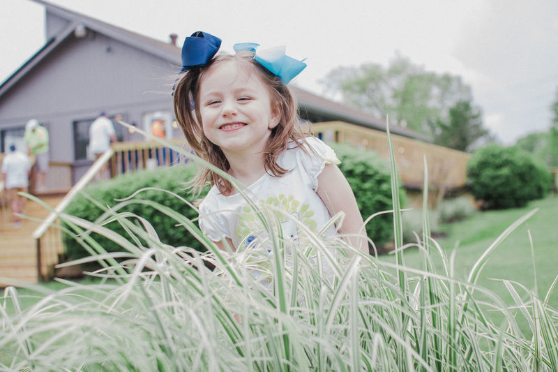 Building Exterior Cheerful Childhood Cute Day Elementary Age Girls Grass Happiness Hide And Seek Lifestyles Looking At Camera One Person Outdoors People Portrait Real People Smiling Surprise