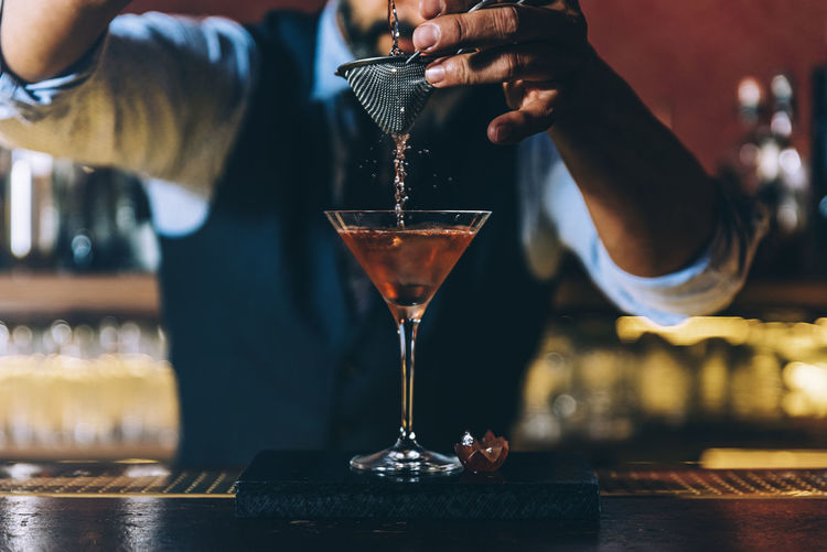 Midsection of bartender preparing cocktail in bar