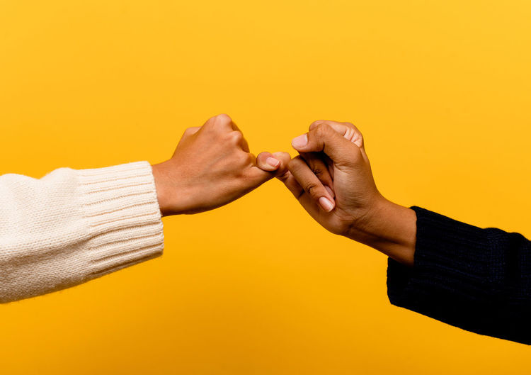 Close-up of woman hand against yellow background