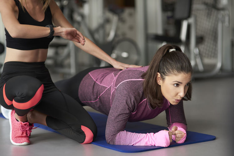 Instructor assisting woman doing plank in health club