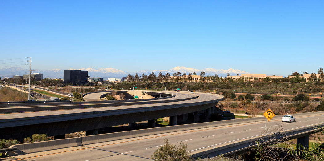 Highway exit headed from Newport Beach into Irvine, California, USA, with white-capped mountains in the distance and a blue sky above. Architecture California City Cityscape Clear Sky Day Highway Irvine, California. Modern Mountains Newport Beach, CA, USA No People Outdoors Road Travel Tree Urban Skyline