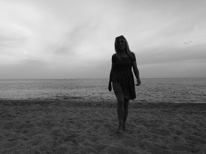 Portrait of woman walking at beach against cloudy sky