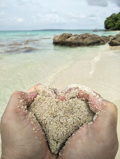 Cropped hands forming heart shape with wet sand at beach