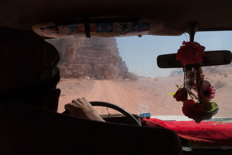Driver's hand on steering wheel, driving through the desert of Wadi Rum 4x4 Desert Driver Driving Adventure Close-up Day Desert Road Desert Track Dirt Track Driving Around Land Vehicle Mode Of Transport Mountain Nature One Person Outdoors People Rear View Mirror Sky Steering Wheel Transportation Window Windscreen