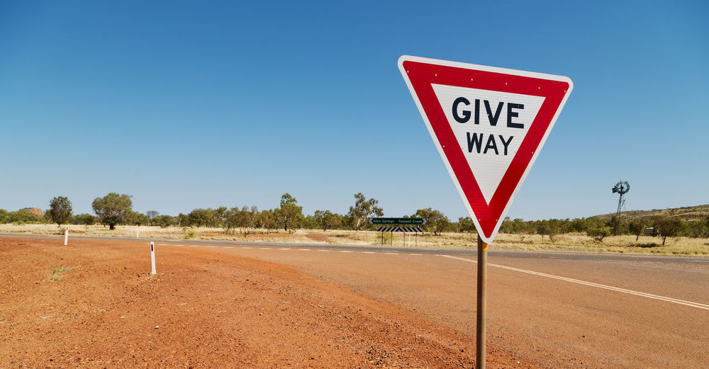 Sign Way Road Australia Give Outback Warning Rural Sky Danger Traffic Nature Direction Australian Symbol Travel Transportation Safety Landscape Idea Planning Major Object Outdoors Country South Old Front Information Control Remote Pole Shape Single Detail Blank Culture Scenic Concepts Highway Order Location Directional Red Black White Dirt Earth Dirt Rocks