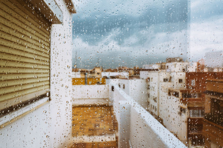 Buildings seen through wet window during rainy season